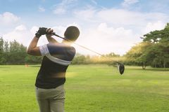 Close up Golfer is driving golf ball to green course with light flare.  royalty free stock photo