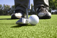 Close up of golfer putting on the green. A close up of a golfer's putter and ball as he gets ready to putt the ball into the hole Stock Photography