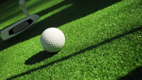 Close-up of golfer using putter to sink short putt into hole stock video footage