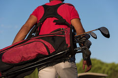 Close up of golfers back while   walking and carrying golf  bag Royalty Free Stock Image