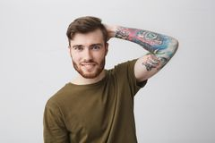 Close up of good-looking cool european guy with beard and arm tattoo smiling brightfully, holding hand behind head with. Cheerful expression, posing for stock images