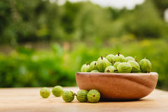 Close-up of gooseberries in vintage wooden bowl on wooden table Royalty Free Stock Photos