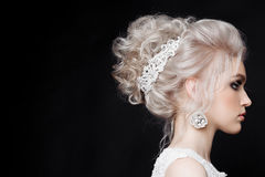 Close up of gorgeous woman with stylish bride haircut of curly blonde hair. Wearing lace dress with shiny elements and earring wit Stock Images