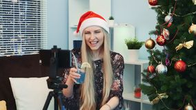 Close up of gorgeous young lady in Santa hat shooting a video blog by smartphone at home. She has a drink in her hands and a Christmas tree on the right stock video