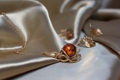 Close-up gouden ketting met tegenhanger van gouden en authentieke Baltische amber op lichtbruine atlas royalty-vrije stock foto