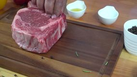 Close up of gourmet chef or cook seasoning fresh chunk of deli piece of beef with sea salt and grounded spicy peppers.  stock video
