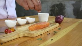 Close up of gourmet chef or cook seasoning fresh chunk of deli piece of salmon fish with sea salt and grounded spicy peppers.  stock video footage