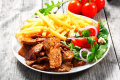 Close up Gourmet Healthy Food on White Plate. Close up Gourmet Healthy Tasty Food on White Plate with Pork, Veggies and Fries, Served on the Top of Wooden Table stock images