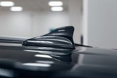 Close-up GPS antenna shark fin shape on a roof of car for radio. Navigation system. Antenna shark fin on blurry background. Car detail stock photo