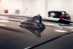 Close-up GPS antenna shark fin shape on a roof of car for radio navigation system stock photography