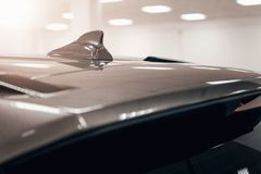 Close-up GPS antenna shark fin shape on a roof of car for radio navigation system. Antenna shark fin on blurry background. Car detail royalty free stock photos