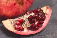 Close up Granate Seeds in slice. Pomegranate Slice Fruit. diet, vitamine and Health concept. Gray board. Close up Granate Seeds in slice. Pomegranate Slice Stock Images
