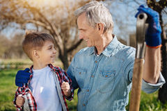 Close up of granddad and child smiling at each other. Two peas in a pod. Two male generations spending free time outdoors in a garden and looking at each other Royalty Free Stock Photography