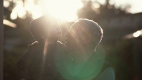 CLose-up of grandfather holding grandson on hands, hugs and kiss boy on cheek. Old man standing outdoor in sunlight. 4K. CLose-up of grandfather holding grandson Stock Image