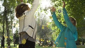 Close-up of grandmother and granddaughter tossing leaves, jumping and spinning around. Two happy caucasian women having. Fun in the autumn park. Joyful family stock video
