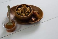 Granola bar and honey on white background Royalty Free Stock Image