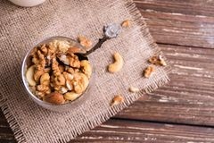 Close up of granola with nut mix. Making healthy breakfast concept. Rustic wooden table background. Top view royalty free stock image