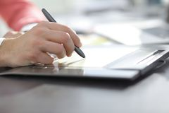 Close up. a graphic designer uses a graphics tablet sitting at D. Esk in Studio stock image