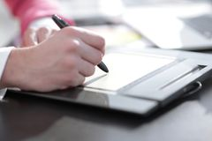 Close up. a graphic designer uses a graphics tablet sitting at Desk in Studio.  royalty free stock image