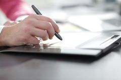 Close up. a graphic designer uses a graphics tablet sitting at Desk in Studio.  stock photos
