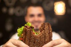 Close-up grappig vaag protrait van jonge mensengreep gebeten sandwich door zijn twee handen Sandwich in nadruk Donkere achtergron royalty-vrije stock afbeeldingen