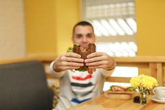 Close-up grappig vaag protrait van jonge mensengreep gebeten sandwich door zijn twee handen Sandwich in nadruk Lichte achtergrond royalty-vrije stock afbeeldingen