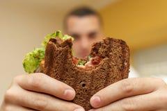 Close-up grappig vaag protrait van jonge mensengreep gebeten sandwich door zijn twee handen Sandwich in nadruk Lichte achtergrond royalty-vrije stock afbeelding