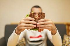 Close-up grappig vaag protrait van jonge mensengreep gebeten sandwich door zijn twee handen Sandwich in nadruk Lichte achtergrond stock foto's