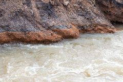 Water flows into gravel, rocks, under the road. Stock Photo