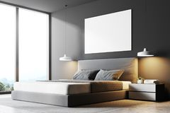 Gray panoramic bedroom corner, poster. Close up of a gray panoramic bedroom with a concrete floor, a double bed and a magnificent window view. A poster on the Royalty Free Stock Photography