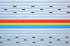 Close up gray, red, yellow, blue metal sheet slide door texture background. Royalty Free Stock Images