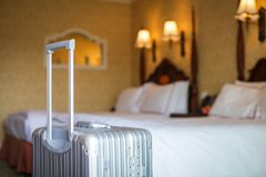 Close up gray silver travel suitcase is in an unoccupied hotel room and there is white linen cover. Close up gray silver travel suitcase is in an unoccupied royalty free stock photo