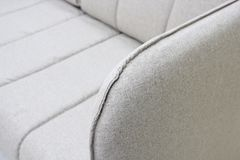Close-up of gray sofa with armrest. Textiles, new furniture modern design. With free space for text. stock photo