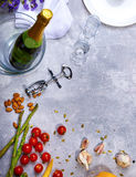 Close-up of a gray table with plate, champagne, tomatoes, asparagus, glasses, corkscrew, flowers on a gray background. Royalty Free Stock Photos