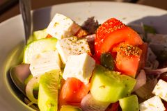 Close up Greek Fresh vegetable salad with white feta cheese. Tomatoes, cucumbers, onion, seasoning and olives in the sunset sun rays at the beach restaurant Stock Images