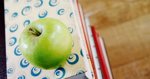 Green apple on book stack. Close-up of green apple on book stack stock footage