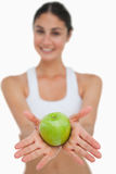 Close-up a green apple holding by a brunette. Against a white background Stock Image