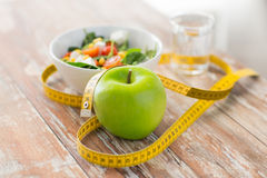 Close up of green apple and measuring tape Stock Photo
