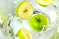 Close up green apples falling in water with splash. stock image