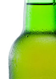 Close-up of a green beer bottle with condensation on white Stock Photography