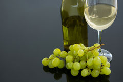 Close-up of green bunch of grapes with glass and bottle of wine Royalty Free Stock Photos