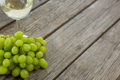Close-up of green bunch of grapes with glass of wine. On wooden table Royalty Free Stock Image