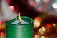 Green burning candle against celebration lights. Close-up of green burning candle against celebration lights. Focus on the flame royalty free stock photography