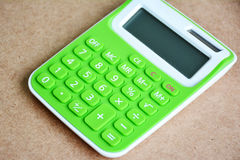 Close up green calculator on wooden table. Stock Photography