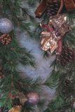 Close up of green christmas wreath with pine cones and silver dauble. In film effect royalty free stock photo