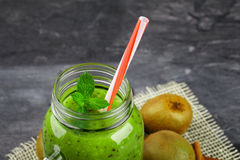 Close-up of a green cocktail. Kiwi smoothie and tropical fruits on a gray background. Cold fruity drink with a straw. Stock Photos