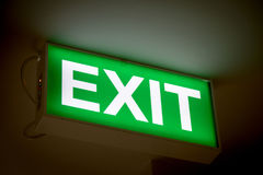 Close up Green Exit sign on door in the building Stock Photos