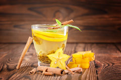 Close-up of green herbal tea on a dark wooden background. A glass cup with carambola, lemon mint leaves and cinnamon. Copy space. royalty free stock image