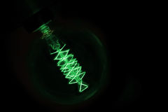 Close up on green light bulb glowing in dark Stock Photos