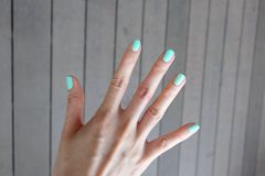 Close Up Green Manicure Nail. Beautiful Female's Hand Nails Polish on the Wood Floor Background Stock Images